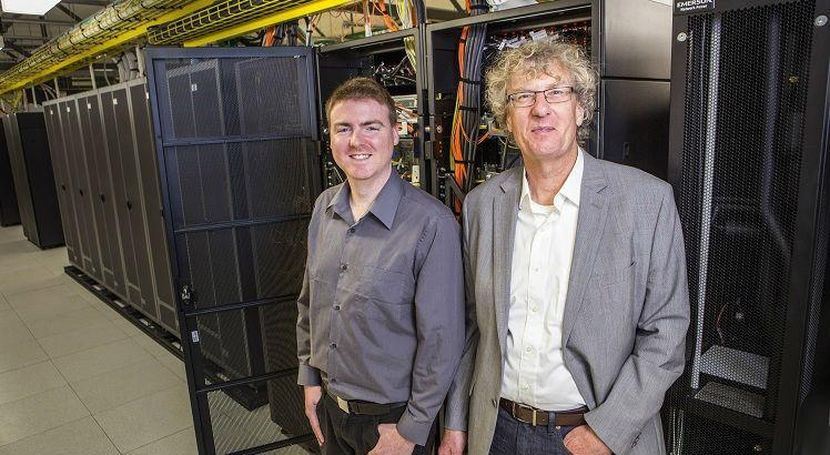"""This handout photo taken on September 6, 2016 and released on September 26, 2016 shows University of Canterbury alumni composer Jason Long (L) and professor Jack Copeland (R) in the UNIVER Blue Gene computer area. New Zealand researchers said on September 26 they have restored the first recording of computer-generated music, created in 1951 on a gigantic contraption built by British genius Alan Turing. / AFP PHOTO / UNIVERSITY OF CANTERBURY / STR / -----EDITORS NOTE --- RESTRICTED TO EDITORIAL USE - MANDATORY CREDIT """"AFP PHOTO / UNIVERSITY OF CANTERBURY"""" - NO MARKETING - NO ADVERTISING CAMPAIGNS - DISTRIBUTED AS A SERVICE TO CLIENTS - NO ARCHIVES"""